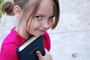 A little girl holds on to her father's Bible outside church.